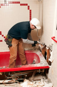 Bathroom remodeler with pry bar doing a demolition job on bathroom in Vancouver WA