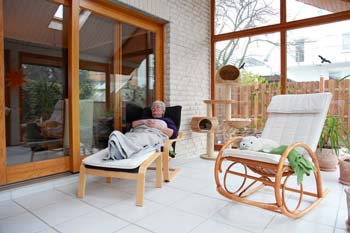 Older Homeowner Relaxing in an Enclosed Porch